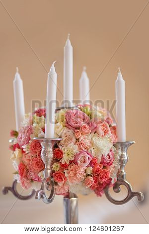 Candlestick. Wedding reception centerpiece close-up with pastel orange and white.