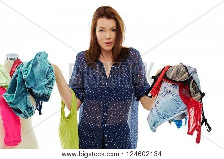 Young woman choosing from different clothes, isolated over white background