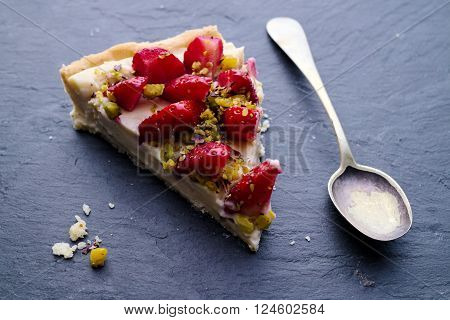 Homemade baked Strawberry tart slice with pistachios, rustic silver spoon and crumbs. Selective focus on middle of tart slice. ** Note: Shallow depth of field