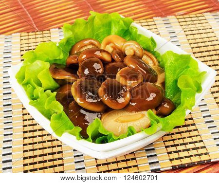 Marinated mushrooms with lettuce leaves. On a white background.