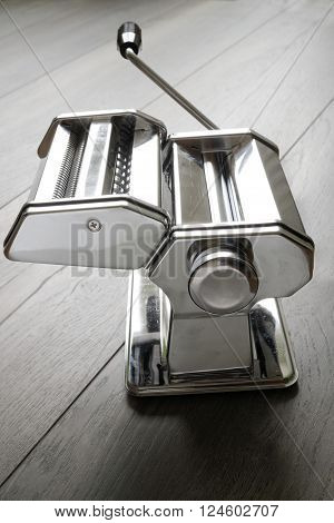 Metal reflective pasta machine with add-on and hand crank wood surface. Selective focus on middle of pasta machine. Concept of food preparation. ** Note: Visible grain at 100%, best at smaller sizes