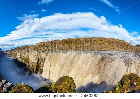 Great Falls Dettifoss in Iceland. Sunset on a summer day, a magnificent rainbow in the water foam