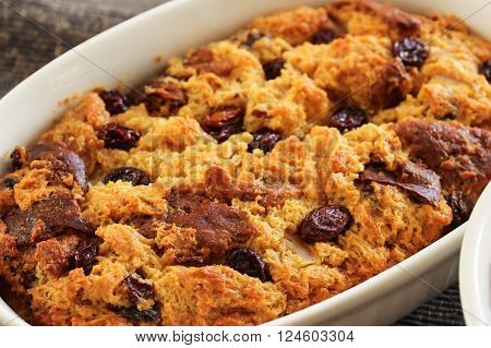 Bread pudding in a white ramekin close up view
