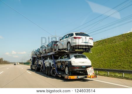 GERMANY - MAR 26 2016: New SEAT cars being transported on a trailer on German autobahn on a sunny spring day
