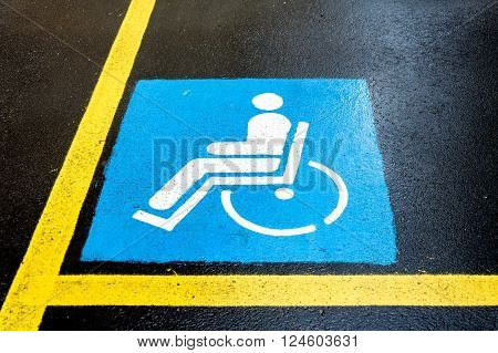 Wheelchair Handicap Sign on dark asphalt road street background- handicap parking place