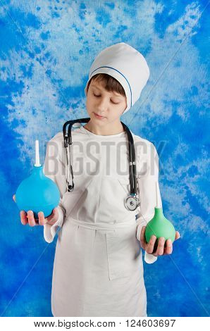 Boy in white doctor costume with stethoscope and two enemas in hands on blue background looking on them