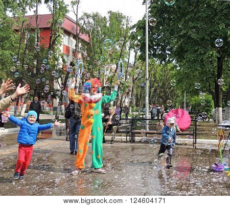 VORONEZH, RUSSIA - May 16, 2015: Children trying to catch bubbles created by the clown in the town square during the literary festival. May 16, 2015 in Voronezh, Russia