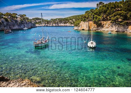 The fjords between stony coast. White sailing yachts wait for the owners.  National Park Calanques on the Mediterranean coast