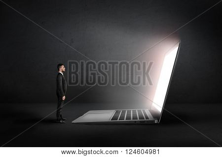 A businessman stands in front of an open glowing huge laptop looking at it in the darkness. Profile view.