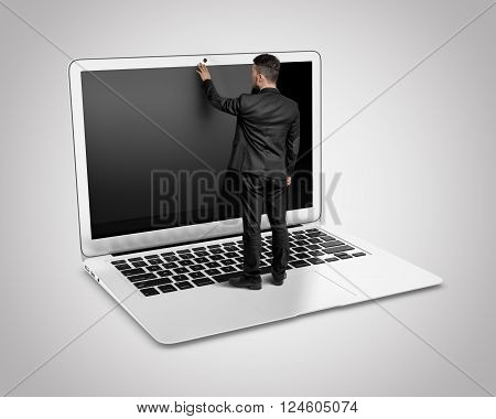 A businessman standing on a big laptop keyboard with blank screen touches the monitor by his hand.