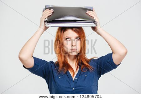 Exhausted overworked redhead young woman standing with folders on her head over white background
