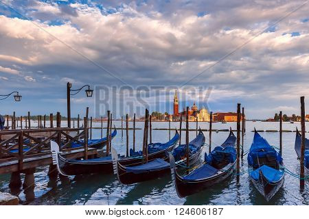 Gondolas moored by Saint Mark square with San Giorgio di Maggiore church in the background  during sunset, Venice, Italia