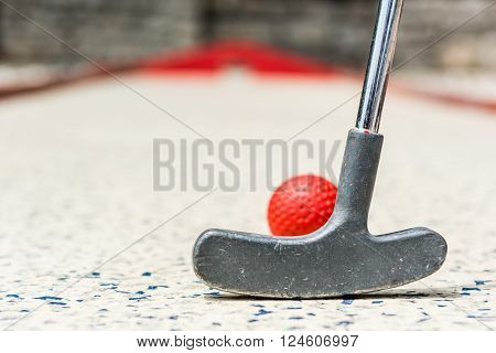 Closeup of red mini golf ball. Strike concept.
