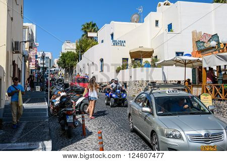 THIRA, SANTORINI, GREECE  - AUGUST 25, 2015: Street of Thira with many tourists and transport at Santorini island.