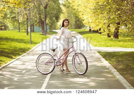Young Girl In Sundress Riding A Bicycle In Park