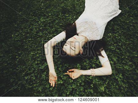 Young White Girl In Sundress Lying On Green Grass In Garden