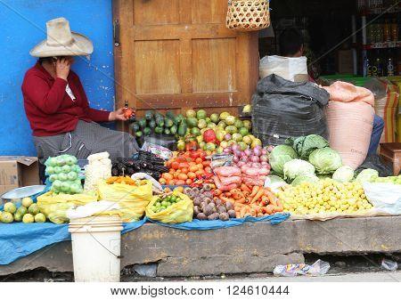 CAJAMARCA PERU - APRIL 1: Sierra woman selling vegetables on Cajamarca, Peru city street while talking on her cellular telephone on April 1 2016.