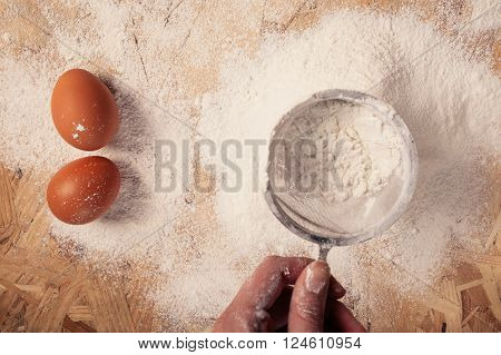 white flour and eggs on a wooden background Girl throws the flour through a sieve view from above