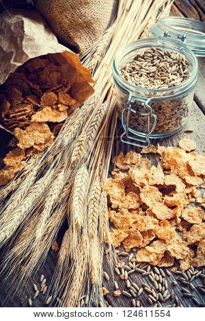 Cereal wheat flakes spikes and rye grain on wooden table
