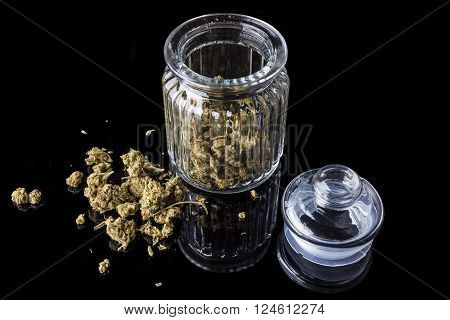 Medical cannabis buds in an open glass jar with marijuana flowers scattered aside and transparent lid on black background from high angle