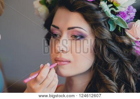The visagist is applying wedding makeup. Beautiful Bride Portrait wedding makeup wedding hairstyle Wedding dress