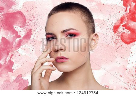 Young Woman bald short hair with Clean Fresh Skin close up. Beautiful Spa Woman Smiling. Perfect Fresh Skin Youth and Skin Care Concept colorful watercolor blots in the portrait and the background