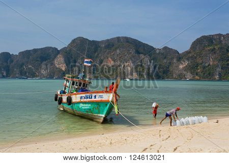 PHI PHI DON, THAILAND - MARCH 2: Traders of drinking water coming by wooden boat to tropical village on March 2, 2015. Tropical Ko Phi Phi National Park covers about 39000 hectares