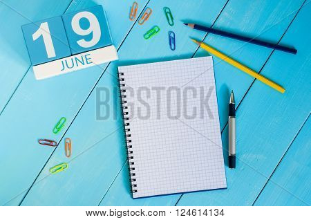 June 19th. Image of june 19 wooden color calendar on blue background. Summer day. Empty space for text.