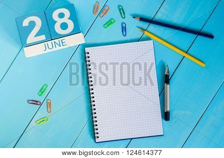 June 28th. Image of june 28 wooden color calendar on blue background. Summer day. Empty space for text.