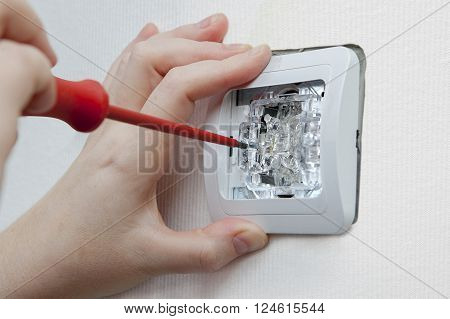 Changing room wall light switch installation with a screwdriver, close-up electrician hands