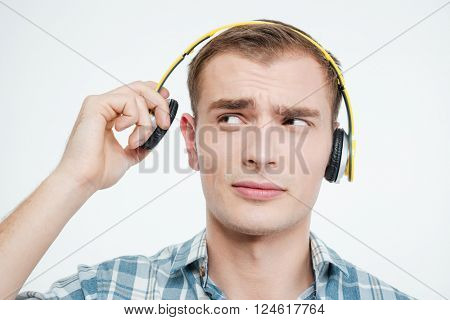 Unhappy handsome young man taking off headphones over white background