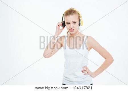 Unhappy stressed young woman listening to music too loud and removing yellow headphones over white background