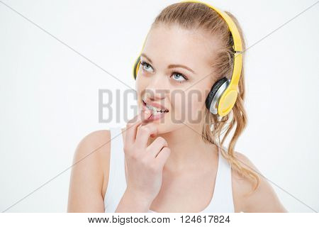 Pensive tensed young woman listening to music in yellow headphones over white background