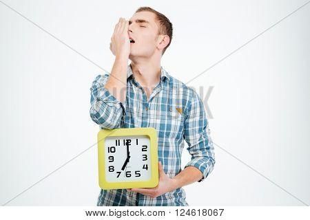 Sleepy tired man yawning and holding clock over white background