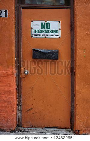 Old creepy door with no trespassing sign