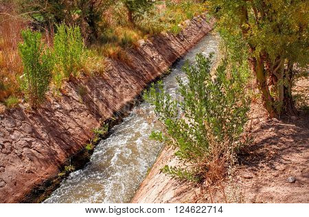 Fast-Moving Desert River Aqueduct with Shrubs and Dirt ** Note: Soft Focus at 100%, best at smaller sizes