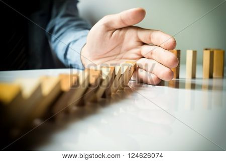 businessman hand stop dominoes continuous toppled or risk with copyspace