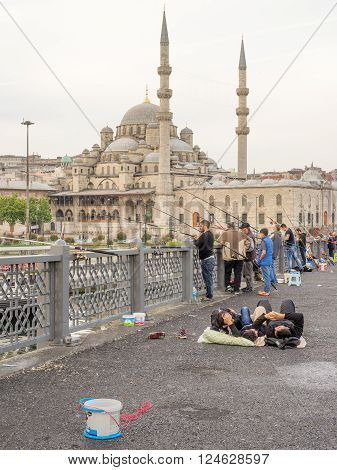 Istanbul Turkey - Jun 28 2015: In early morning three people were lying on Galata Bridge ground chatting while other people were fishing meters away. The New Mosque was in the background.