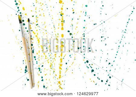 Two paint brushes with colorful gouache sprays and splashes on a white background. Art composition.