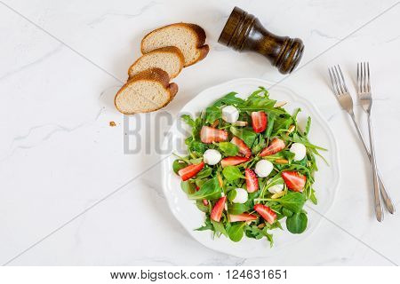 Healthy green salad with arugula, spinach, strawberries, almonds and mini mozzarella cheese balls on plate on white background, table top view food