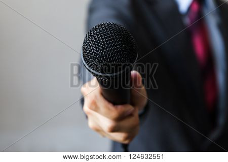 Man in business suit holding a microphone conducting a business interview journalist reporting public speaking press conference MC