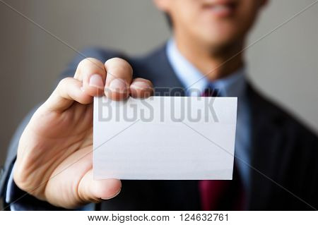 Young Man In Business Suit Holding White Blank Business Card. Business Name Card Presenting (mock Up