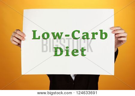 Woman holding paper with Low-Carb Diet text on color background