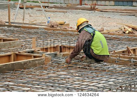MALACCA, MALAYSIA -OCTOBER 13, 2015: Construction workers fabricating steel reinforcement bar at the construction site in Malacca, Malaysia