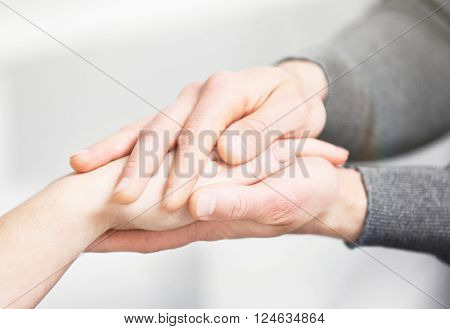 Man and woman holding hands closeup