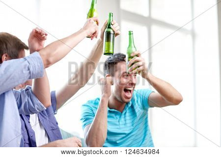friendship, leisure, people and alcohol concept - close up of happy male friends drinking beer and celebrating victory at home
