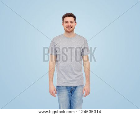 male, gender, fashion and people concept - smiling young man in gray t-shirt and jeans over blue background