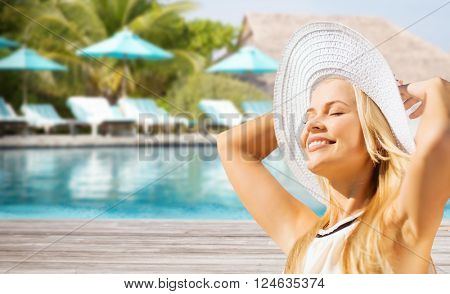 people, summer holidays, travel, tourism and vacation concept - beautiful woman in sun hat enjoying summer over exotic hotel resort beach with swimming pool and sunbeds background