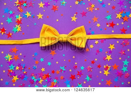 yellow bow tie and confetti on a purple background