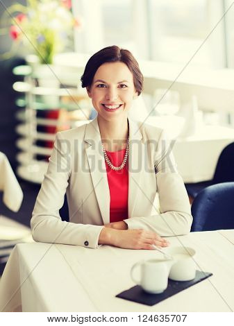 people, women, business and lifestyle concept - happy woman sitting at table in restaurant